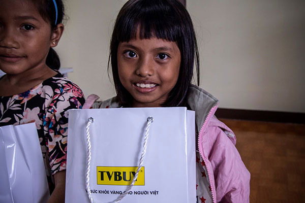 Một học sinh vui vẻ khi nhận được quà tặng của TVBUY